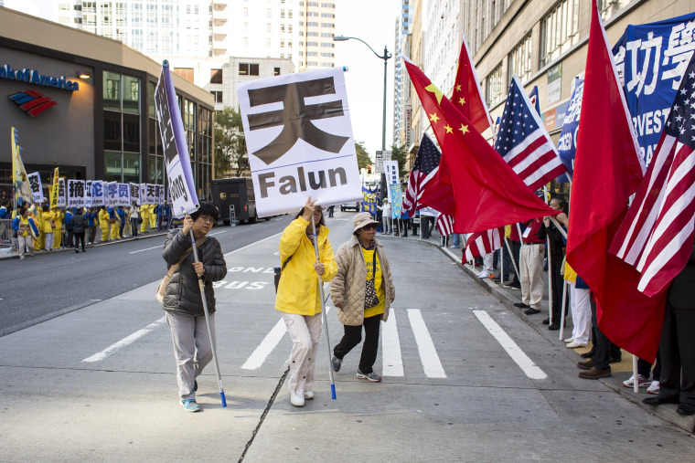 Practitioners of Falun Gong, who say the religious movement is persecuted in China, protest the visit of Chinese President Xi Jinping as counter protestors wave Chinese and U.S. flags in Seattle, Washington, September 22, 2015.