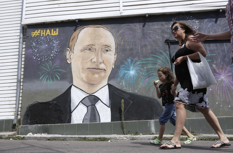 Image: People walk past a mural depicting Russia's President Vladimir Putin