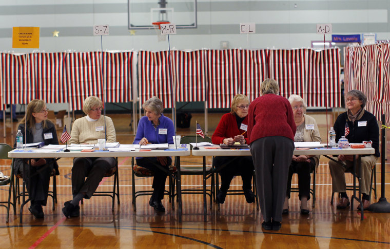 Image: Election volunteers await voters at a polling station in Nashua, New Hampshire