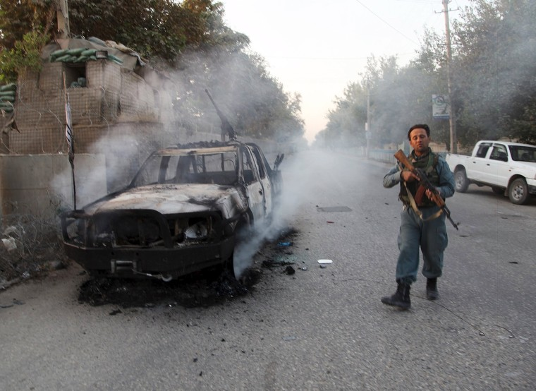 Image: An Afghan police officer patrols near burning car in Kunduz