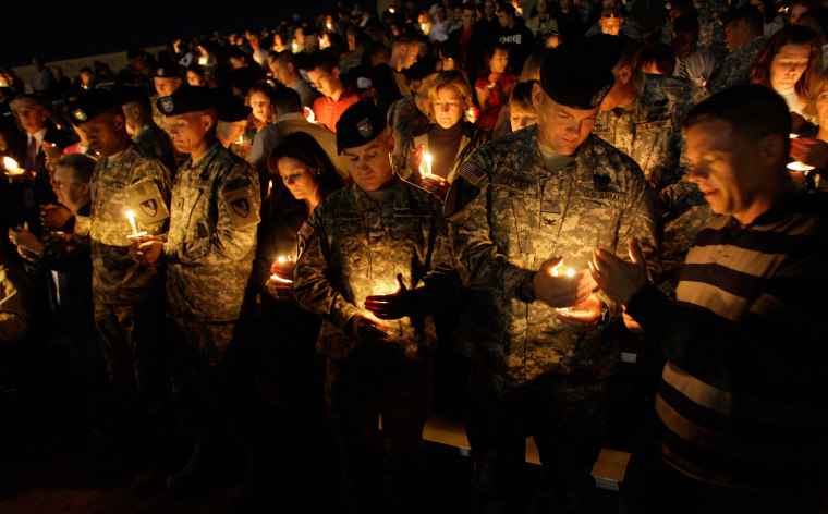 Image: Soldiers hold a candle light vigil