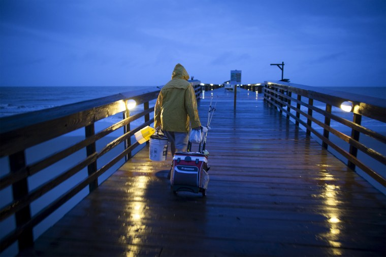 Image: Fisherman Dominick Manfredini prepares to fish at daybreak at the pier at Myrtle Beach State Park