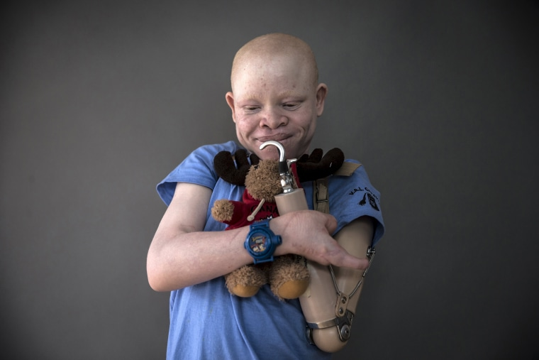 Image: Festo from Tanzania poses for a portrait with a plush toy that he says makes him feel safe at night and that he sleeps with, in the Staten Island borough of New York in the Staten Island borough of New York