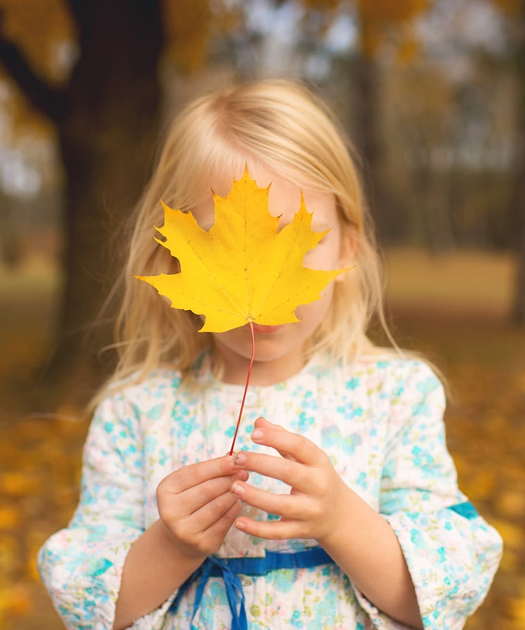 Allowing your child to find the biggest leaf she can, then hide her face behind it is one of Wilkerson's suggestions for interesting leaf pile photos.