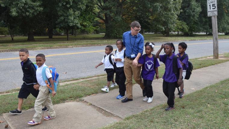 Teacher walks children home.