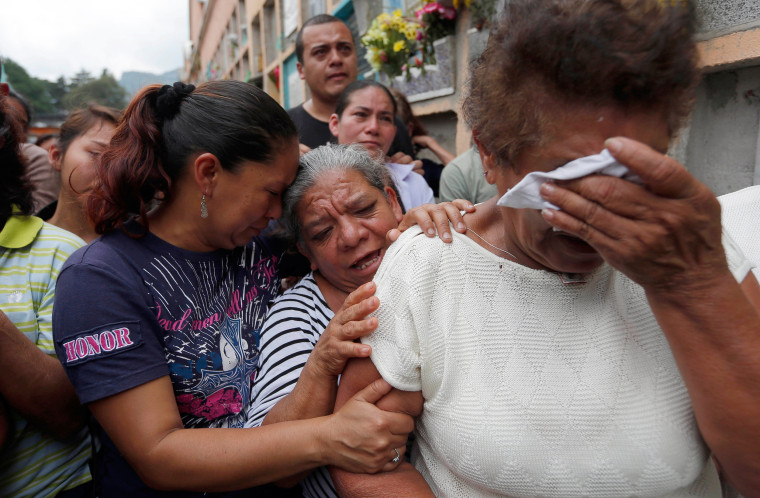 Image: Relatives weep during the burial of a landslide victim