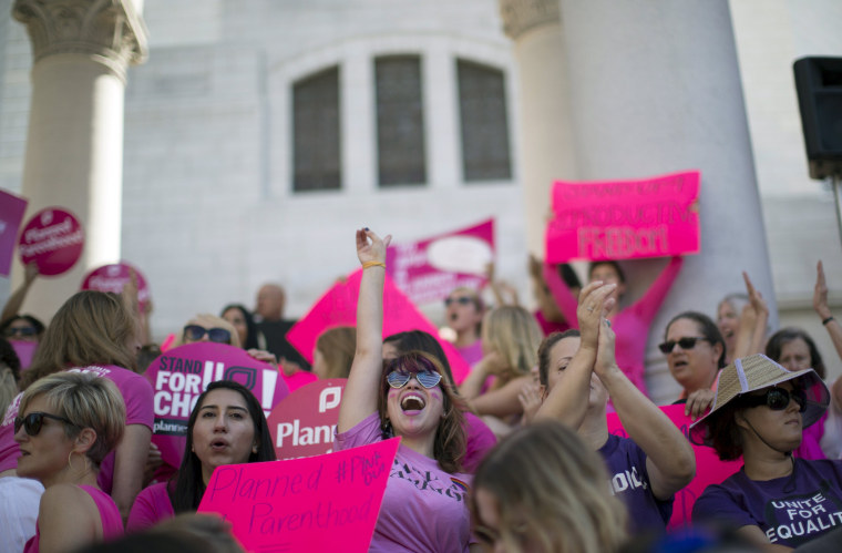 """Image: Activist Weismer chants during a rally in support of Planned Parenthood on """"National Pink Out Day"""" on the steps of City Hall in Los Angeles"""