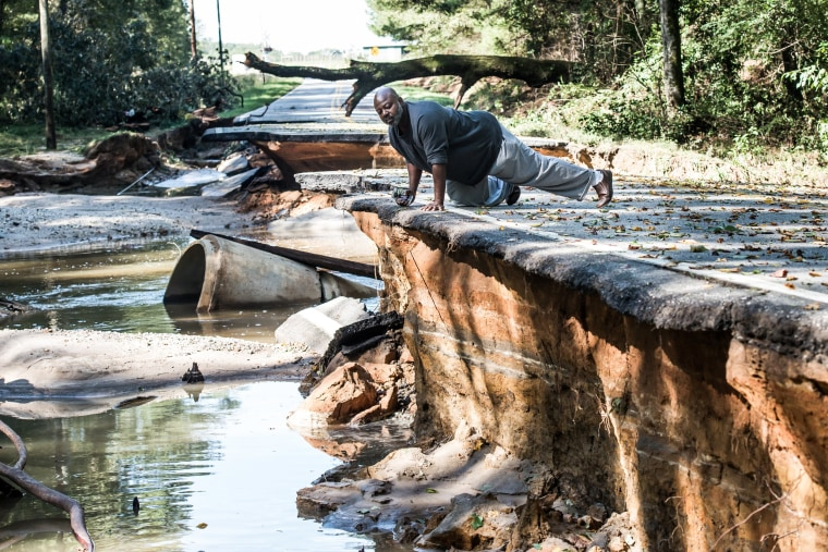 Image: A man observes severe road damage after floodwaters recede