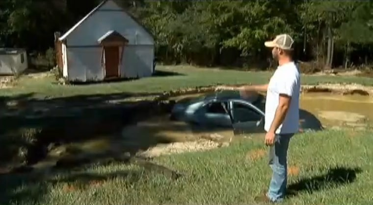 Travis Catchings surveys the spot where he his grandmother's car ended up after Sunday's flood.