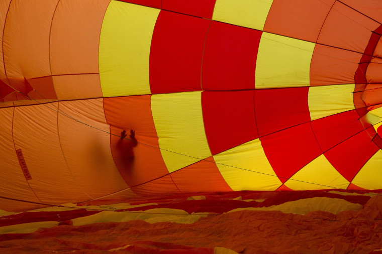 Image: An attendee touches the outside of an inflating hot air balloon during the 2015 Albuquerque International Balloon Fiesta in Albuquerque, New Mexico