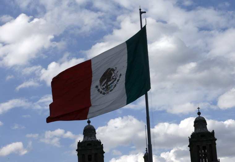 Image: Mexico's flag flutters next to the Metropolitan Cathedral at Zocalo Square in Mexico City