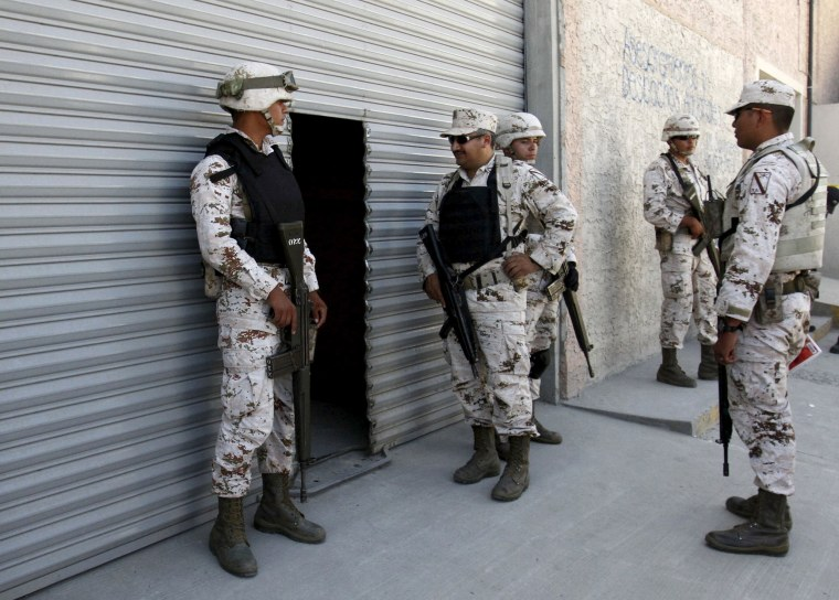 Image: Soldiers of the Mexican Army stand guard outside a warehouse containing a tunnel discovered by Mexican Army, in Tijuana