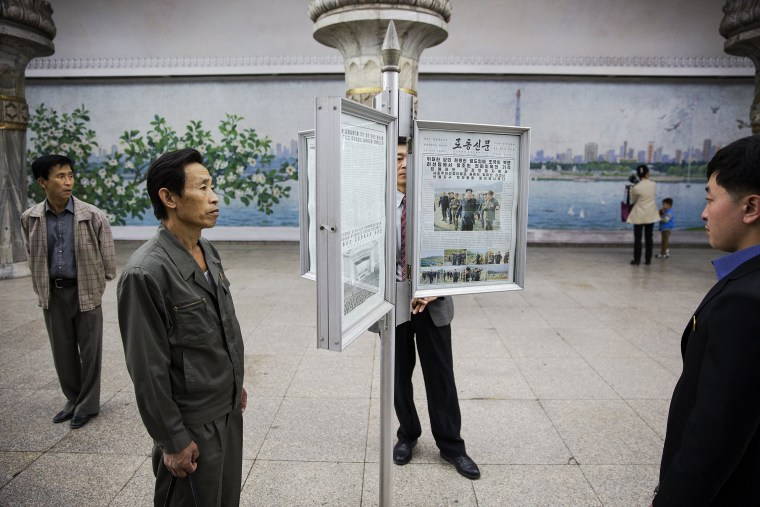 Image: People read newspapers displayed inside a subway station visited by foreign reporters during a government organised tour in Pyongyang