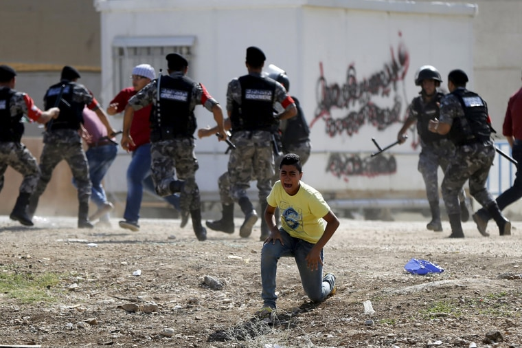 Image: A civilian yells as riot policemen clash with protesters near the Israeli Embassy in Jordan
