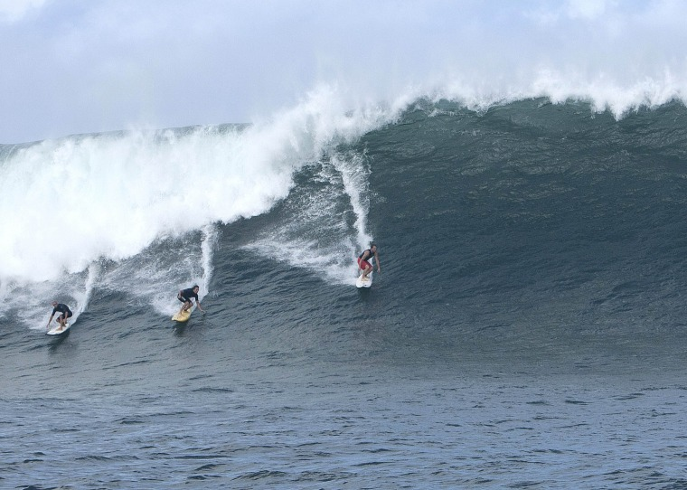 Image: Three surfers catch a large wave at the surf spot on the outer reefs known as 'Himalayas