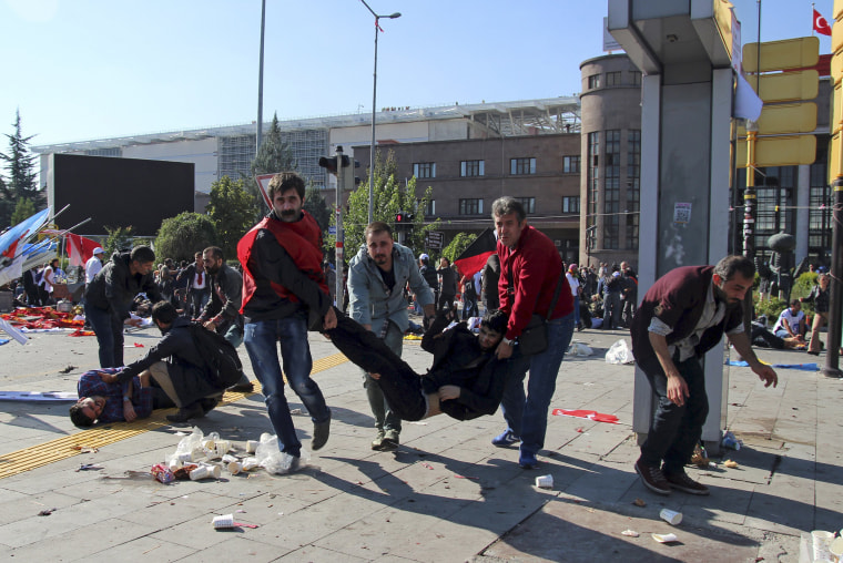 Image: People carry an injured man after an explosion during a peace march in Ankara