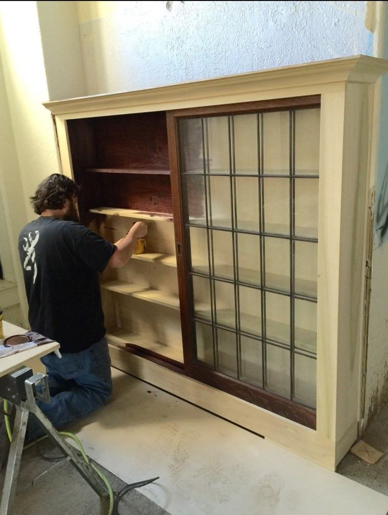 Aaron Gray, one of the Singing Contractors, paints wood stain onto cabinets he built.