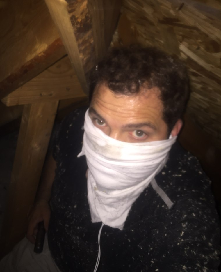 Who is that masked man? It's the Singing Contractors' Josh Arnett, who protects himself while doing mold remediation treatment in an attic.