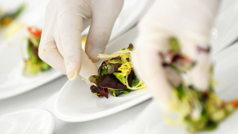 Gloved hand serving food