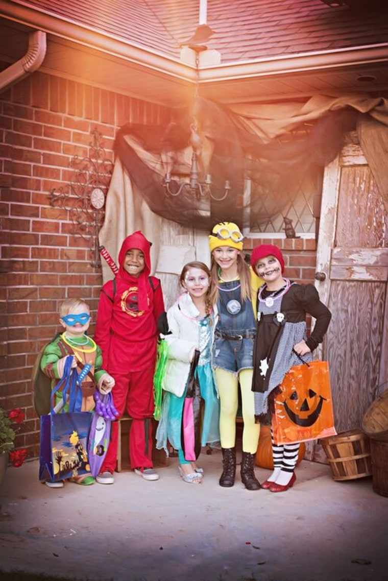 Taking a group shot of your kids and their trick-or-treating buddies can be a great way to get kids to hold still for a photo on Halloween night.