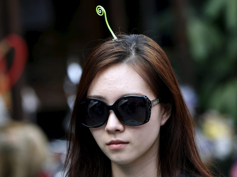 A woman wearing a sprout-like hairpin makes her way on Nanluoguxiang street in Beijing