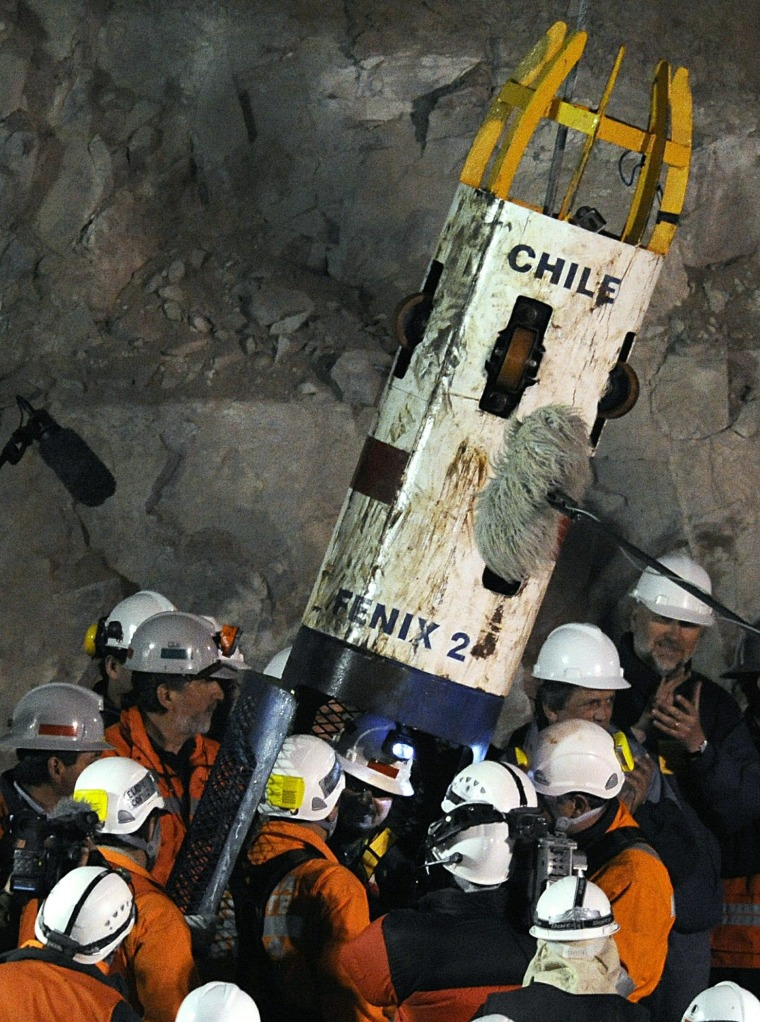 Image: Chilean miner Juan Aguilar (C) talks to