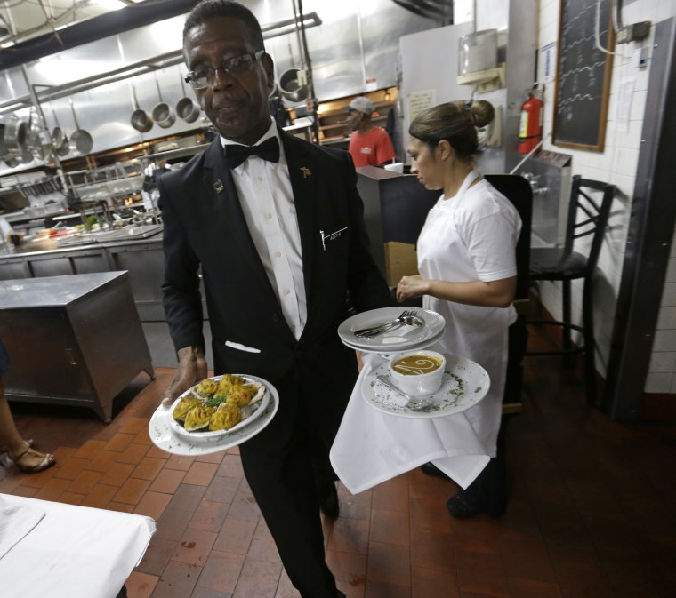 Image: Waiter brings dishes to dining room