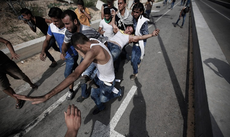 Image: Palestinians carry a wounded youth during clashes with Israeli troops
