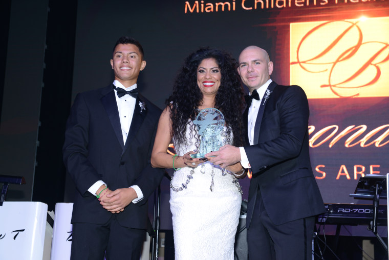 Nicholas Lopez-Morillo and Lucy Morillo, President and CEO, Miami Children's Health Foundation present an award to Armando Christian Perez.