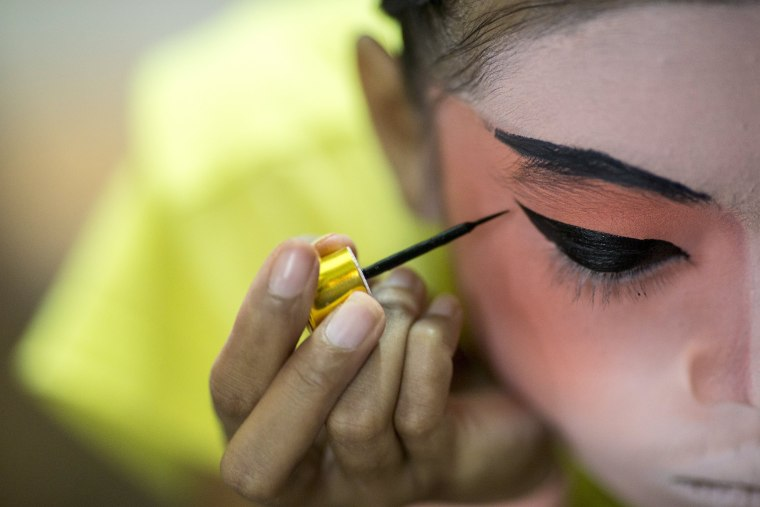 Image: A member of a Chinese opera troupe applies make-up before performing at a shrine during the annual vegetarian festival in Bangkok