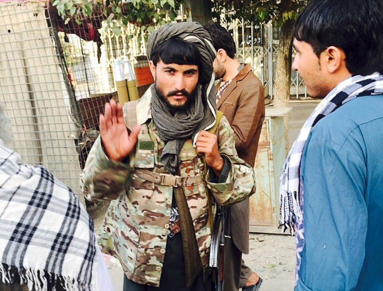 Image: A Taliban fighter talks with residents of Kunduz, Afghanistan