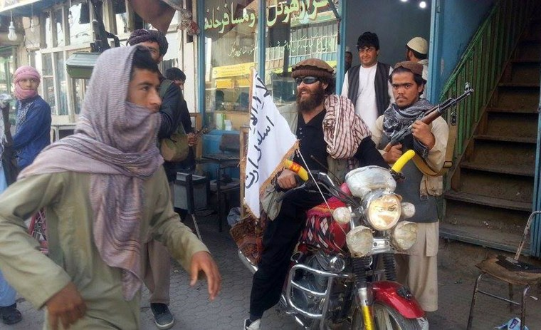 Image: A fighter sits on a motorcycle adorned with a Taliban flag