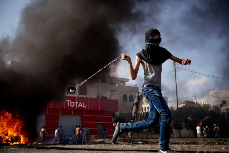 Image: A Palestinian hurls a stone during clashes with Israeli troops near Ramallah