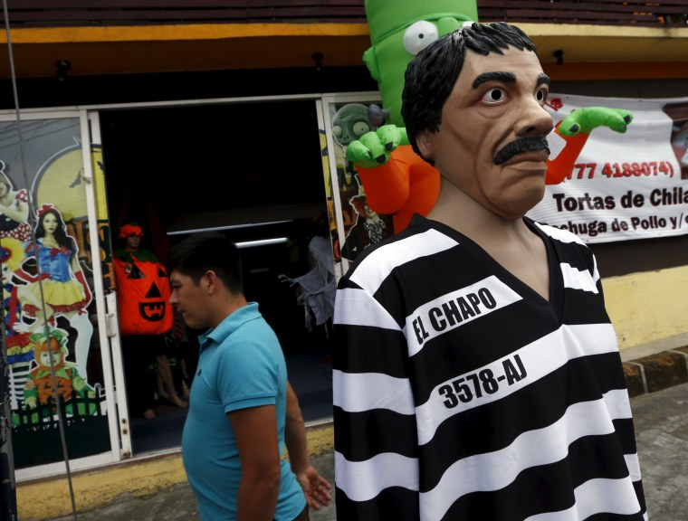 Image: A man walks past a Guzman costume on display at the front of a shop, in the Mexican city of Cuernavaca near Mexico City