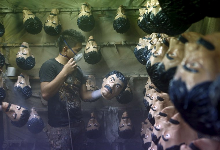Image: A employee sprays Guzman masks at Grupo Rev in the Mexican city of Cuernavaca near Mexico City