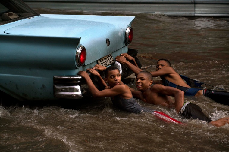 Image: Youths hang from the rear bumper of a vintage American car in Havana