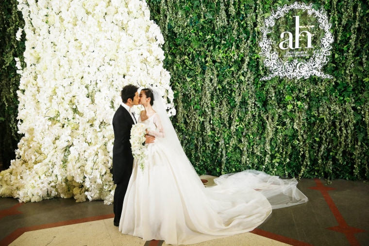 Image: Actor Huang Xiaoming and actress Angelababy pose during their wedding
