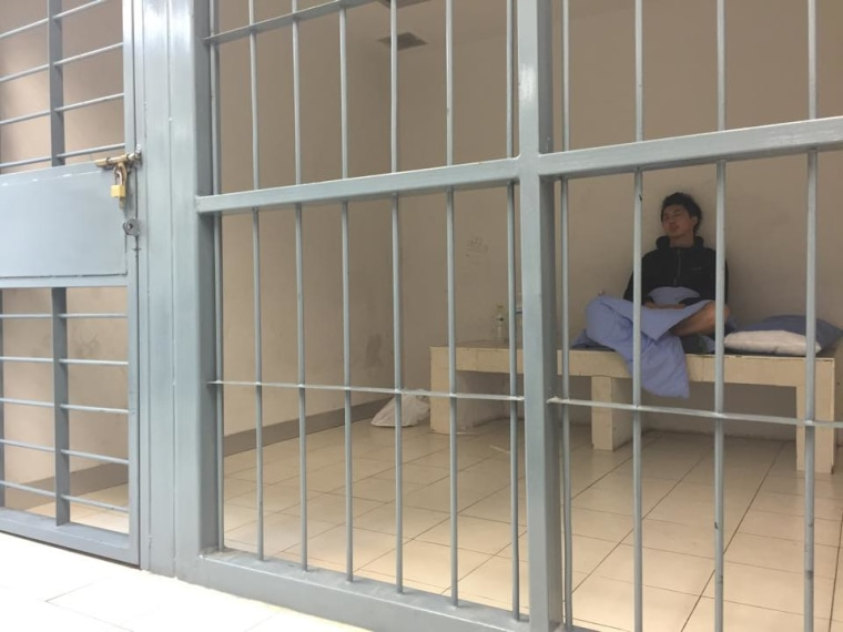 Hong Kong journalist Hok Chun Anthony Kwan sits in a cell Monday, Aug. 24, 2015, after he was detained Sunday at Suvarnabhumi Airport in Bangkok, Thailand, for carrying body armor and a helmet onto a flight bound for Hong Kong. Kwan, who was in Bangkok covering the aftermath of last week's bombing, is being charged with possessing an illegal weapon, which carries a prison sentence of up to five years.