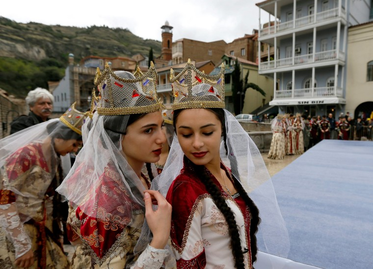 Image: Young Georgian musicians wearing traditional outfits chat during 'Tbilisoba' celebrations
