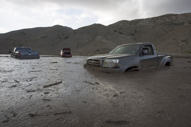 Image: Cars and trucks remain mired in mud and debris on State Route 58 near Tehachapi