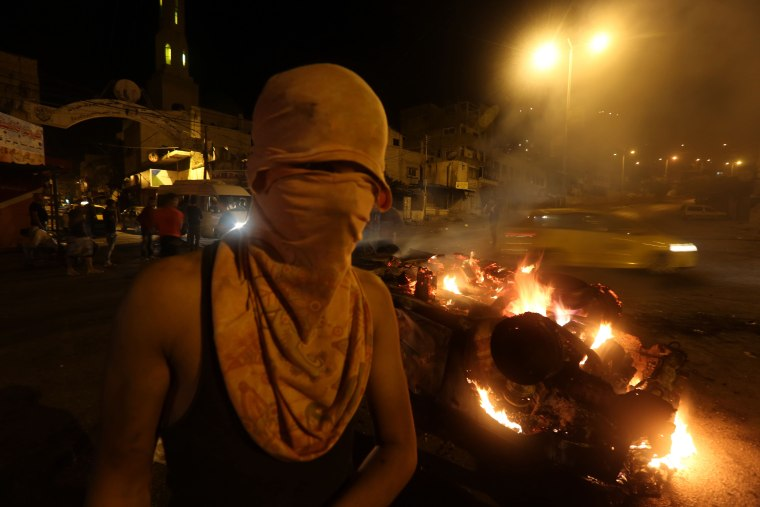 Image: Palestinian youth stand next to a burning car belonging to an Israeli settler