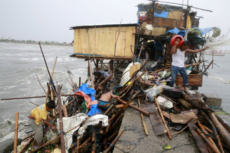 Image: A Taroyo family living along the coast of Manila Bay searches for salvageable items after their house was damaged  by strong winds brought by typhoon Koppu