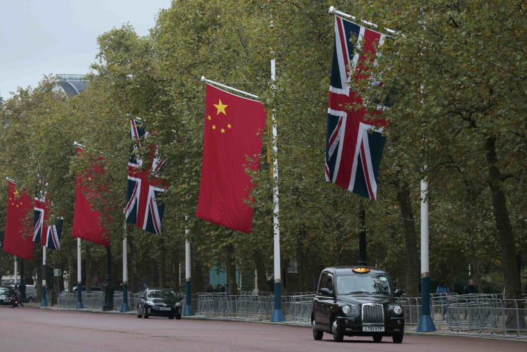 Image: A taxi drives past Chinese and British flags on the Mall in London