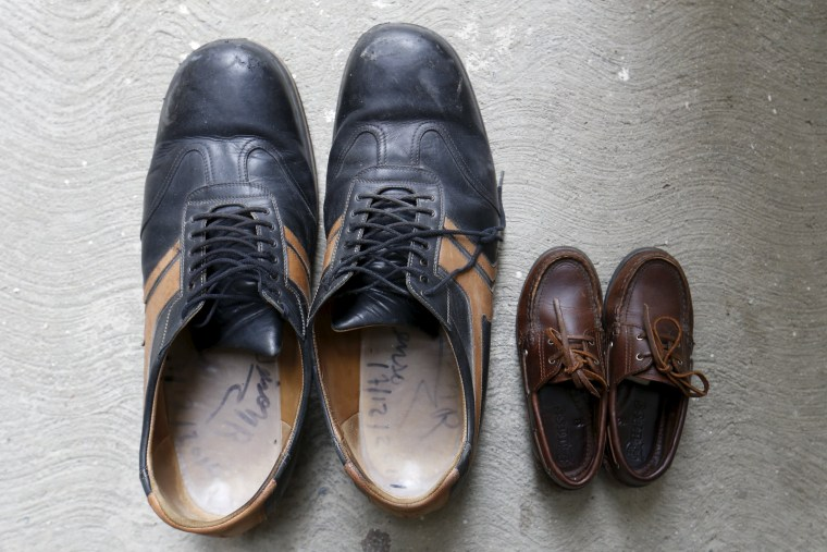 Image: The shoes of Jeison Rodriguez (L), the living person with the largest feet in the world, are seen next to the shoes of his nephew at his house in Maracay, Venezuela