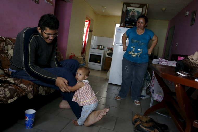 Image: Jeison Rodriguez (L), 19, the living person with the largest feet in the world, holds his niece Osmariel with the help of his foot at his house in Maracay, Venezuela