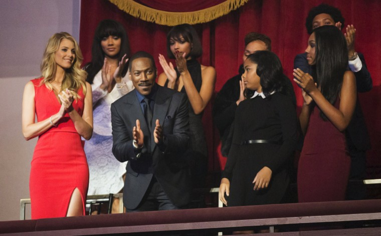 Image: Eddie Murphy, his partner Paige Butcher and members of his family applaud as he takes his seat for the Mark Twain prize for Humor honoring him at the Kennedy Center in Washington