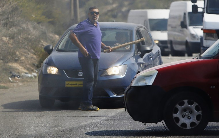 Image: An Israeli motorist holds a club before he was struck by a Palestinian vehicle in the West Bank city of Hebron