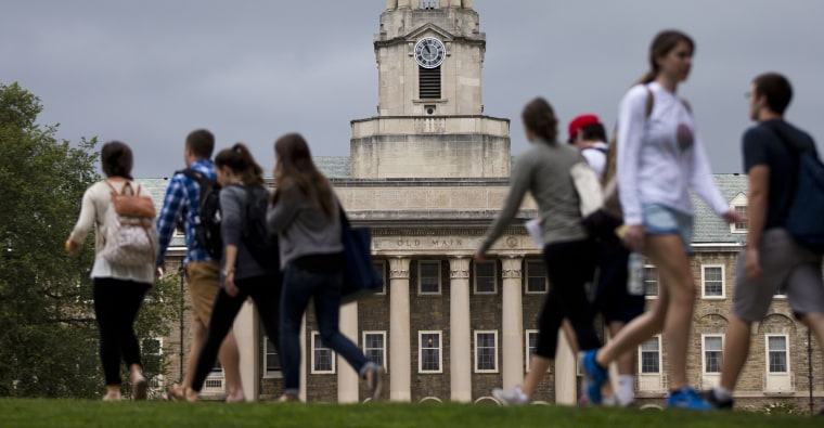 Students walk past the Old Main building on the Penn State campus Tuesday, Sept. 9, 2014, in State College, Pa.
