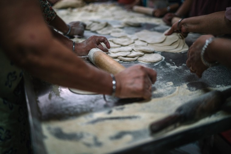 Women makes chapatis at the Sikh Temple in Richmond Hill, Queens on Sunday, October 11th 2015.