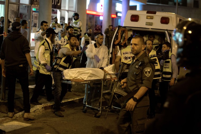 Image: Medics carry the covered body of an Israeli man